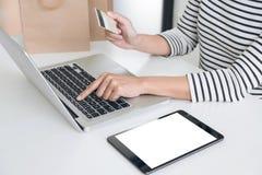 Mani del ` s della donna facendo uso del registro della carta di credito e dello sho online di pagamenti Fotografia Stock