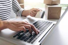Mani del ` s della donna facendo uso del registro della carta di credito e dello sho online di pagamenti Fotografie Stock Libere da Diritti