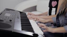 Mani del ` s della ragazza sulla tastiera del piano La ragazza gioca il piano, fine sul piano Mani sulle chiavi bianche del piano archivi video