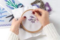 Mani del ` s delle donne con un incrocio ricamato sui modelli del tessuto dei fiori Immagini Stock Libere da Diritti