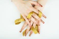 Mani del ` s delle donne con un nastro dorato in sue dita su fondo bianco Fotografia Stock