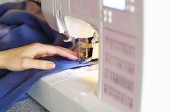 Mani del ` s delle donne della cucitrice che usando macchina per cucire Adattamento del Proc fotografia stock libera da diritti