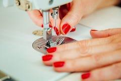 Mani del ` s delle donne sul lavoro con la macchina per cucire Fotografie Stock Libere da Diritti