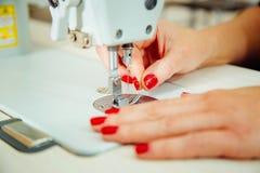 Mani del ` s delle donne sul lavoro con la macchina per cucire Fotografia Stock