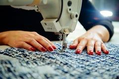 Mani del ` s delle donne sul lavoro con la macchina per cucire Immagine Stock