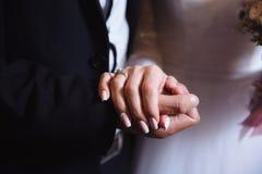 Mani del ` s dello sposo e della sposa con le fedi nuziali sulla tavola marrone Fotografie Stock Libere da Diritti