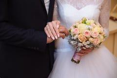 Mani del ` s dello sposo e della sposa con le fedi nuziali sulla tavola marrone Fotografie Stock