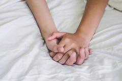 Mani del sesso sul letto, concetto dell'amante delle coppie circa amore, sesso e immagine stock