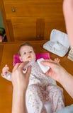 Mani del siero di versamento della madre per pulire gli occhi del bambino Fotografie Stock