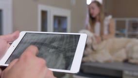 Mani del veterinario del primo piano con i raggi x del ` s del cane sul touchpad video d archivio