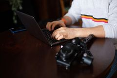 Mani del videographer o del blogger dell'uomo con il computer portatile e la macchina fotografica fotografia stock