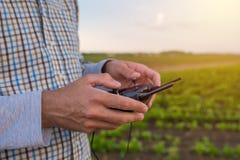 Mani dell'agricoltore che per mezzo del telecomando del fuco Fotografia Stock Libera da Diritti