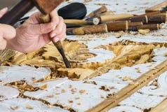 Mani dell'artigiano Working sulla scultura di legno nel modello floreale d'annata Immagini Stock
