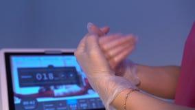 Mani dell'estetista in guanti facendo uso di liquido antisettico per disinfettare stock footage