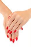 Mani dell'giovani donne. Smalto di chiodo rosso Fotografia Stock