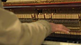 mani dell'uomo anziano nel piano di gioco sotterraneo del sottopassaggio con le corde ed i martelli aperti del og del meccanismo video d archivio