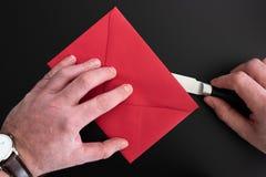 Mani dell'uomo che aprono busta rossa con il tagliacarte fotografia stock libera da diritti