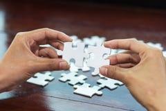 Mani dell'uomo che collegano il pezzo di puzzle delle coppie, immagine stock libera da diritti