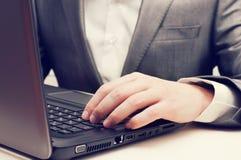 Mani dell'uomo che digitano sulla tastiera del computer portatile Fotografia Stock