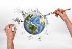 Mani dell'uomo che disegnano una fabbrica e che cancellano gli alberi sul globo Fotografia Stock