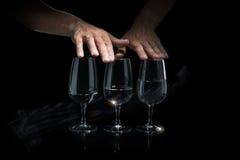 Mani dell'uomo che giocano musica sulle tazze di vetro Immagine Stock