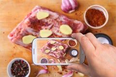 Mani dell'uomo con lo smartphone che prende a foto carne fresca cruda, le costole crude di manzo o dell'agnello con pepe, aglio,  fotografia stock libera da diritti