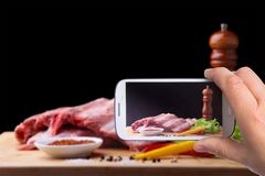 Mani dell'uomo con lo smartphone che prende a foto le costole crude su un tagliere rustico con sale, pepe e la smerigliatrice per fotografia stock libera da diritti