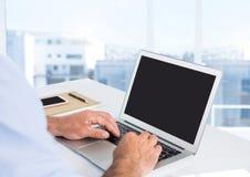 Mani dell'uomo d'affari allo scrittorio con il computer portatile con fondo luminoso Immagine Stock Libera da Diritti