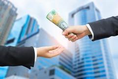 Mani dell'uomo d'affari che passano la banconota del dollaro australiano (AUD) Fotografie Stock Libere da Diritti