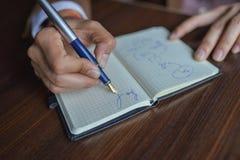 Mani dell'uomo d'affari con il taccuino di scrittura della penna sulla fine di legno della tavola dello scrittorio su Concetto di Immagini Stock