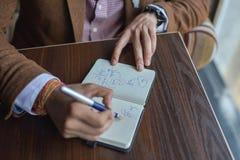 Mani dell'uomo d'affari con il taccuino di scrittura della penna sulla fine di legno della tavola dello scrittorio su Concetto di Fotografia Stock Libera da Diritti