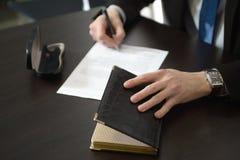 Mani dell'uomo d'affari con il taccuino di scrittura della penna sulla tavola della scrivania Fotografia Stock Libera da Diritti