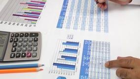 mani dell'uomo d'affari con scrittura della penna e del calcolatore e le carte della limatura sulla tavola stock footage