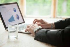 Mani dell'uomo d'affari facendo uso del computer portatile del pc, funzionante con le statistiche, clos Immagine Stock Libera da Diritti