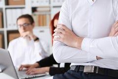 Mani dell'uomo d'affari nel luogo di lavoro attraversato Fotografie Stock Libere da Diritti