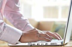 Mani dell'uomo d'affari sulla battitura a macchina della tastiera del computer portatile Fotografie Stock Libere da Diritti