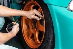Mani dell'uomo del meccanico che controllano pressione d'aria della gomma Automobile di manutenzione fotografia stock libera da diritti