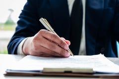 Mani dell'uomo di affari che firmano il capitolato d'oneri immagine stock