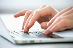 Mani dell'uomo di affari che scrivono su un computer portatile Immagine Stock