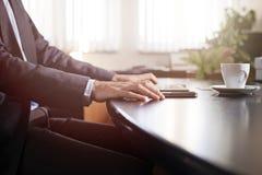 Mani dell'uomo di affari su una tavola con la compressa, il telefono e la tazza di coff Immagini Stock Libere da Diritti