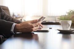Mani dell'uomo di affari su una tavola con la compressa, il telefono e la tazza di coff Immagini Stock