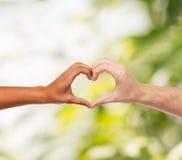 Mani dell'uomo e della donna che mostrano forma del cuore Fotografie Stock