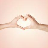 Mani dell'uomo e della donna che mostrano forma del cuore Immagini Stock
