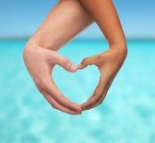 Mani dell'uomo e della donna che mostrano forma del cuore Immagine Stock