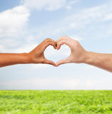 Mani dell'uomo e della donna che mostrano forma del cuore Fotografia Stock
