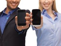 Mani dell'uomo e della donna con gli smartphones Immagini Stock Libere da Diritti