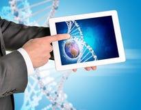 Mani dell'uomo facendo uso del pc della compressa Immagine di terra e di DNA Fotografie Stock Libere da Diritti