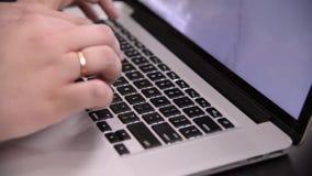Mani dell'uomo nel tipo a quadretti della camicia sulla tastiera nera del taccuino grigio archivi video