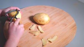 Mani della bambina che sbucciano le patate con lo sbucciatore sullo scrittorio di legno video d archivio
