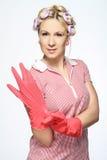Mani della casalinga con i guanti su bianco Immagini Stock